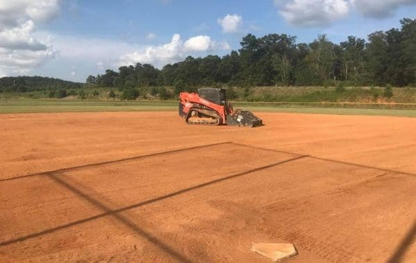 Skid steer conditioning a baseball field