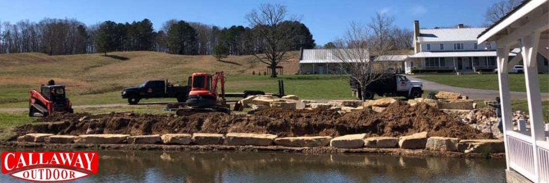 Natural rock retaining wall being built around a lake
