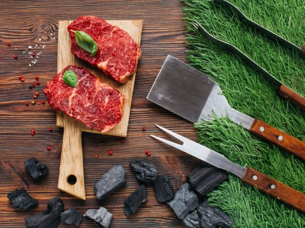 Two steaks on a cutting board with cooking utensils to the right on artificial turf.